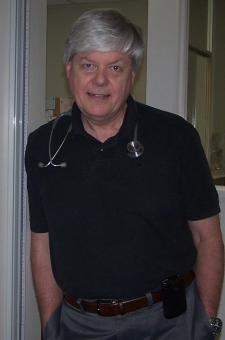 Dr. Miller leaning on a door frame and smiling for the camera