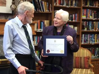 Craig standing in the Winston Park Library next to Her Honour Elizabeth Dowdeswell who is holding a certicificate