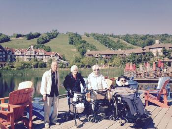 Residents Roy, Shirley, Nancy, and Jack taking a group photo in front of a lake, with the Collingwood hills and resort behind them
