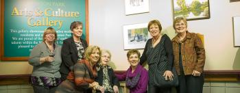 Margaret Dallaire sitting in between her six daughters in front of the Winston Park gallery