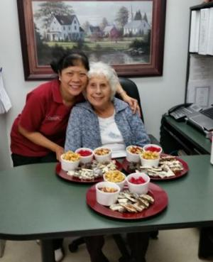Erlinda leaning down with an arm over a female resident who is sitting at a table with three trays of food in front of her