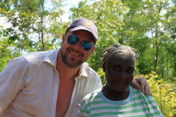 Kristian posing outside in Haiti with Anne, a CLM member