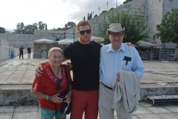 Two residents and a team member posing for a photo amid ruins in Greece