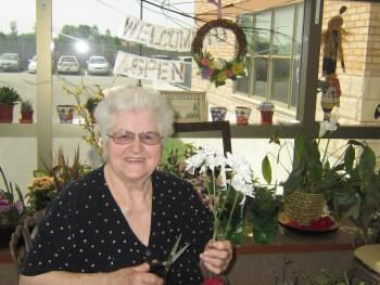 Trudy sitting in the greenhouse snipping the stem of a flower