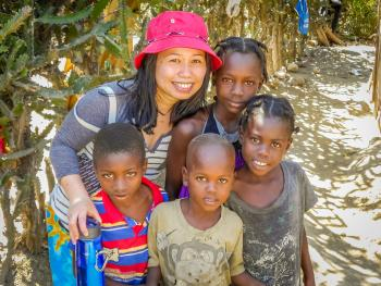 Team member with her arms around a group of small children in Haiti