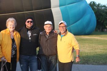 Four people stand in front of a hot air balloon being inflated behind them