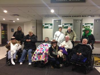 Group of residents and team members bundled up n a hockey arena waiting area