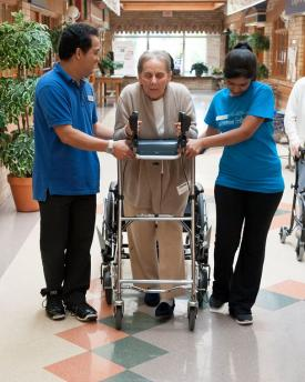Two team members on either side of a resident, assisting her to walk with a walker