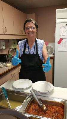 Team Member Sheila giving the thumbs up as she serves lunch