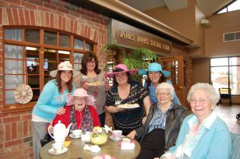 Group of residents and team members posing for a photo in colourful hats
