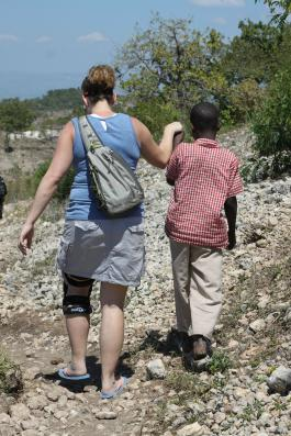 The back of a team member and child in Haiti walking hand in hand on the shore