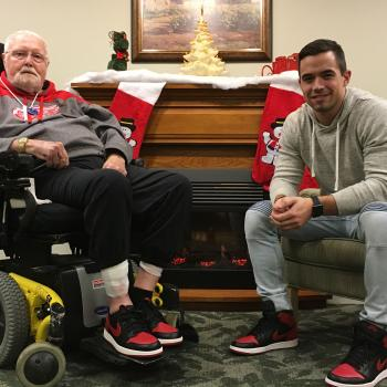William sitting in his wheelchair and Jake sitting in a chair wearing matching red sneakers