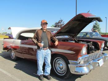 Aspen Lake resident Dan Kinney standing in front of his red '56 Chevy Bel Air in a parking lot