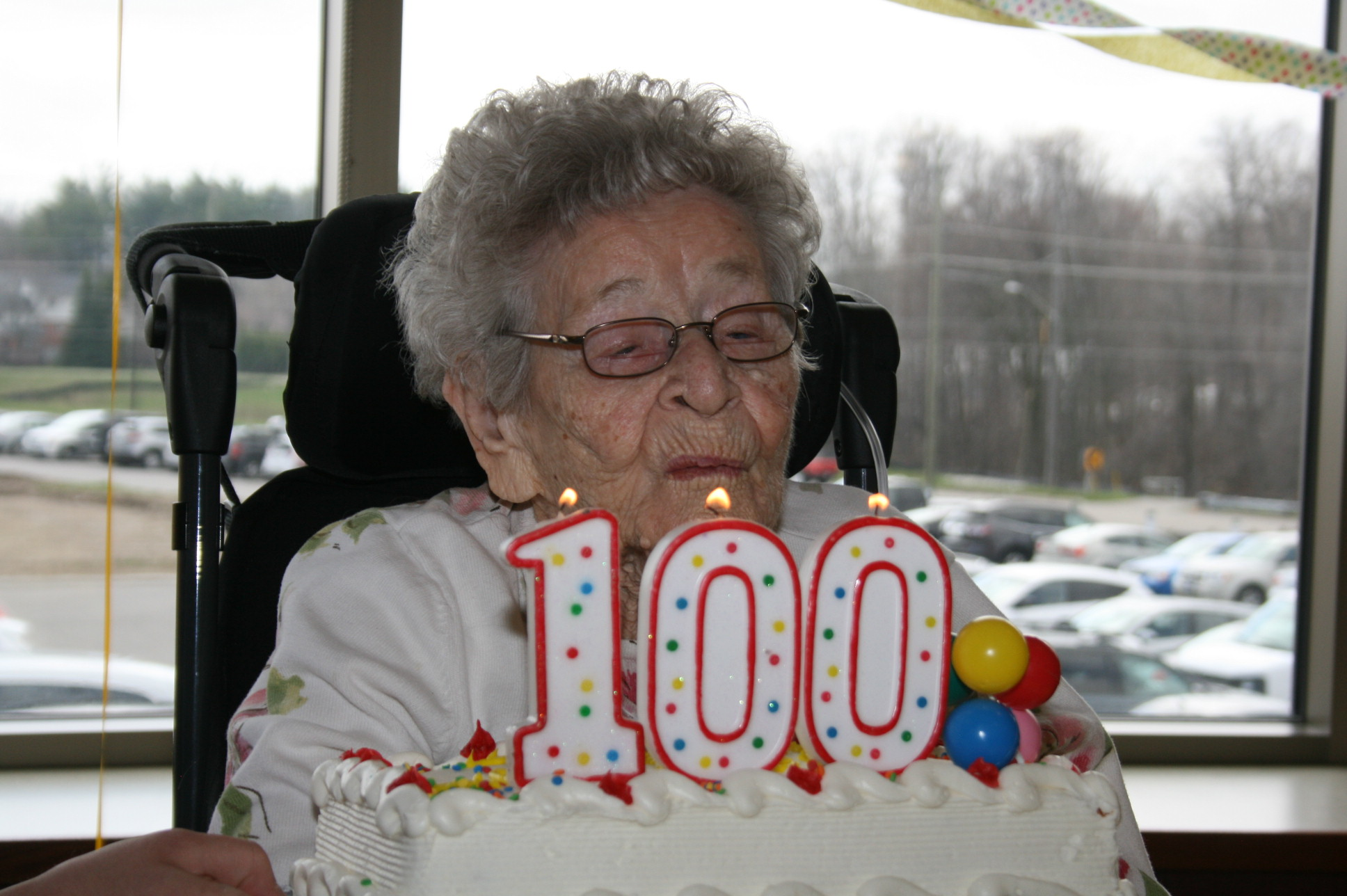 Dot blowing out candles that day 100 on her birthday cake