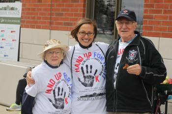 Barbara Skipper, Dagmara Klisz and John Pennington wearing Hand Up for Haiti t-shirts, posing for a photo outside