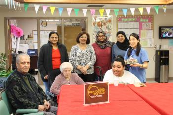 Residents and team members sitting and standing around a table for a group photo inside the village
