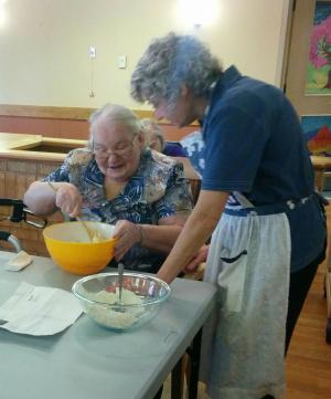 Team member standing next to a sitting resident who is mixing something in  a mixing bowl