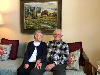 Jean and warren sit together in their suite at Riverside Glen.