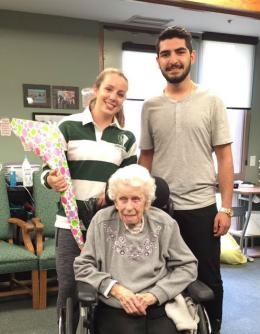 Co-op student Laura holding a bouquet of flower, with her future prom date Ramtin, standing behind resident Laura who is sitting in her wheelchair
