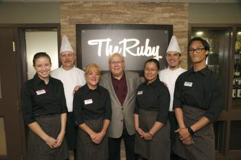 Ron Schlegel and team members standing in front of a sign for The Ruby restaurant