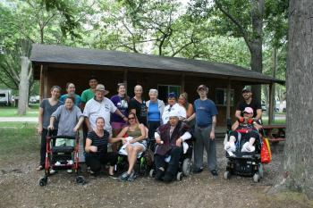 Residents and Team Members in a group photo outside of their cabin