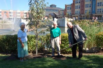 Two residents and Ron Schlegel planting a tree