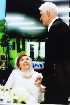 Brenda wearing white while sitting and Brian holding her hand and wearing a suit